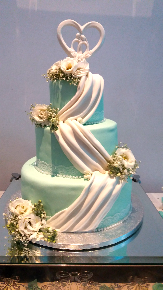 Three tier blue wedding cake with white swag effects - tamworth