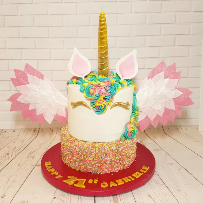 Two tier unicorn theme cake with wings and sprinkles - tamworth
