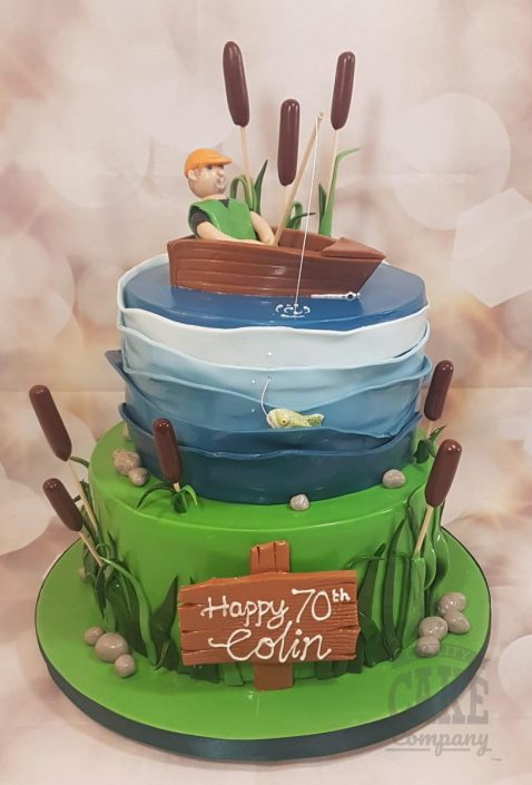 Two tier fishing theme birthday cake with man in boat - tamworth