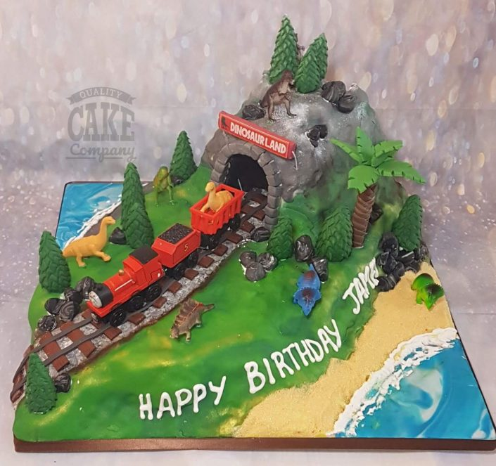 train going through dinosaur land birthday cake - tamworth