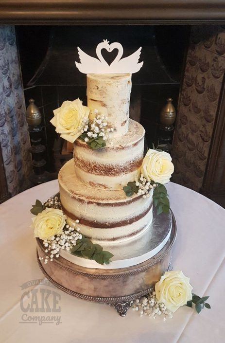 three tier semi naked rustic wedding cake with white roses and swan cake topper - tamworth west midlands