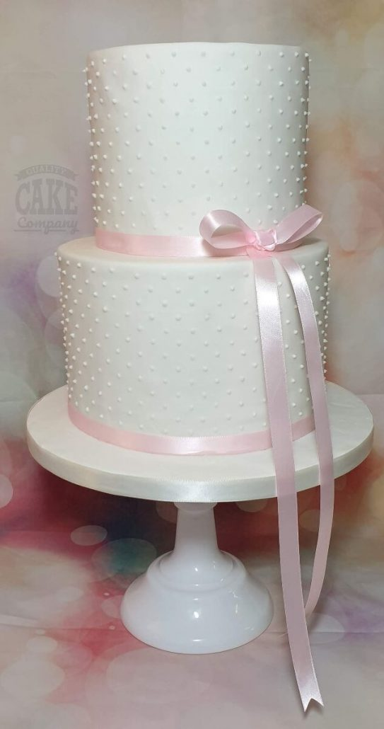 Two tier plain white cake with piped dots and pink ribbon simple elegant cake - Tamworth