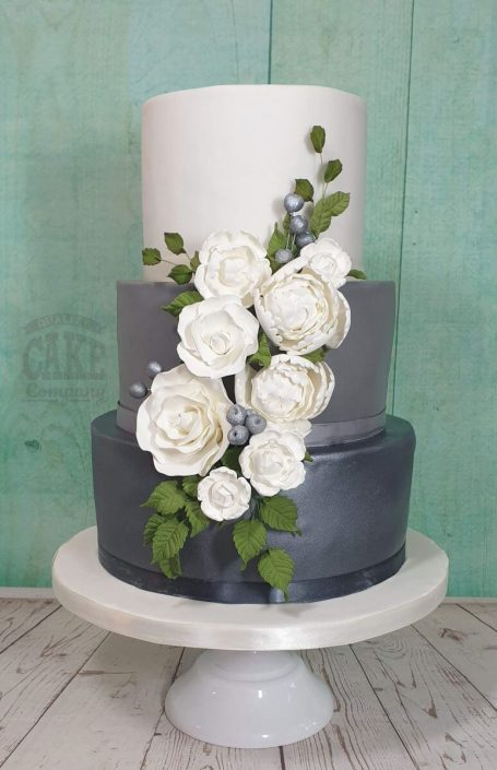Three-tier ombre wedding floral cake greys and silvers with white peonies