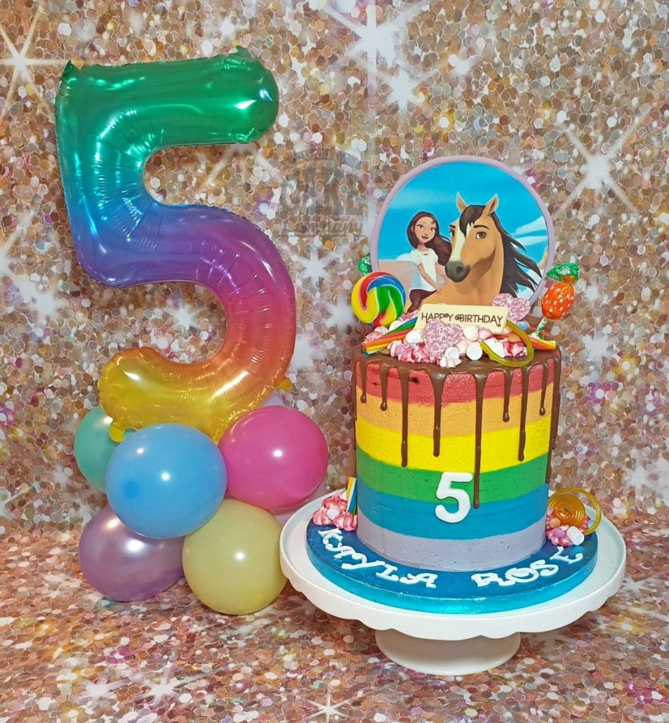 Rainbow buttercream drip cake and matching balloon table display
