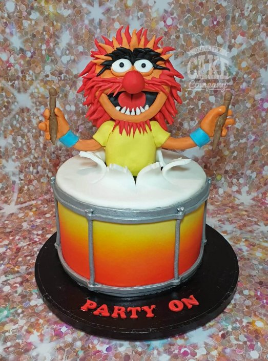 Animal the muppet bursting out of drum theme cake - Tamworth